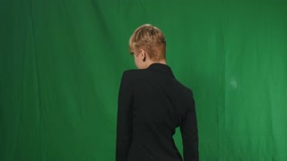 Beautiful model poses for camera at green background