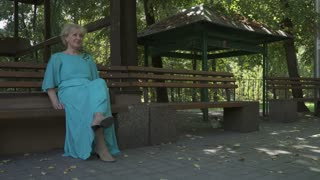 Beautiful old lady in turquoise dress sits on bench