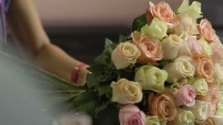 Beautiful roses in female hands, florist makes a bouquet