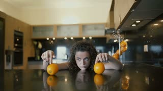Beautiful sad girl playing with oranges on table