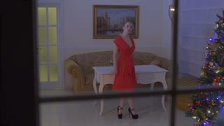 Beautiful sexy woman in red dress dance in the room celebrating Christmas alone