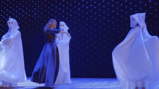 Beautiful singer dances with stranger in cloak on stage in theatre