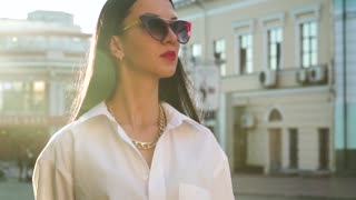 Beautiful stylish brunette in morning sun rays in slow motion at the street