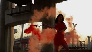 Beautiful stylish woman in red dress dance with red smoke in slowmotion