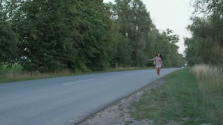 Beautiful woman catches the hitch-hiking car on the road