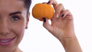 Beautiful woman compares rotten mandarin with problem skin