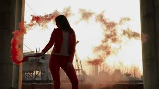 Beautiful woman dancing with red smoke in slowmotion