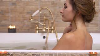 Beautiful woman drinks champagne enjoying of taking a hot bath