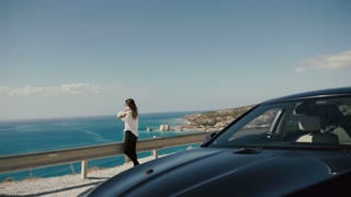 Beautiful woman enjoy the blue ocean near the car