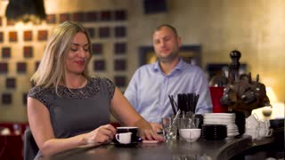 Beautiful woman flirting with handsome man sitting at bar counter in restaurant