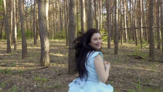 Beautiful woman in blue dress running in the forest, Snow White fairytale