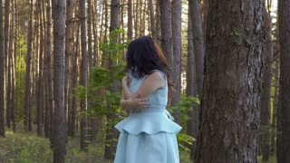 Beautiful woman in blue dress wave off from insects in the forest