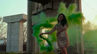 Beautiful woman in dress dancing with green smoke