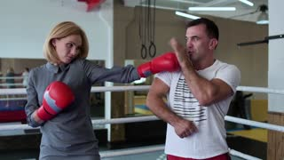 Beautiful woman in elegant dress training with coach at boxing ring
