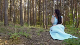 Beautiful woman in long blue dress eat apple in the forest