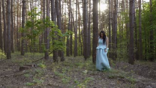 Beautiful woman in long blue dress walks in summer forest