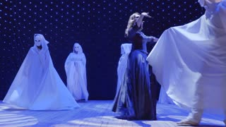 Beautiful woman in long dress are dancing with strangers in cloaks on the scene