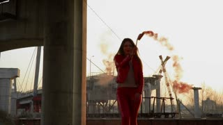 Beautiful woman in red costume dancing with red smoke near abandoned bridge
