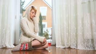 Beautiful woman in sweater sits on floor near window talking by phone