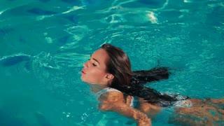 Beautiful woman in white bikini swimming in the blue pool
