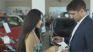 Beautiful woman makes a successful deal of buying car in car dealership