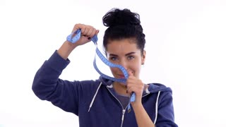 Beautiful woman plays with measure tape at white background
