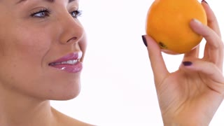 Beautiful woman poses for camera with orange at white background