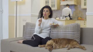 Beautiful woman relax on sofa and eats salad