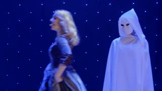 Beautiful woman sing song and dances with strangers in cloaks in theatre