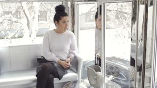 Beautiful woman sit on sofa near the window