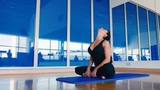 Beautiful woman stretching her back in lotus position on the mat in the gym