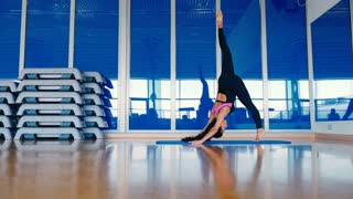 Beautiful woman training flexibility in the gym on mat