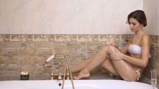 Beautiful woman washes her body with shower gel