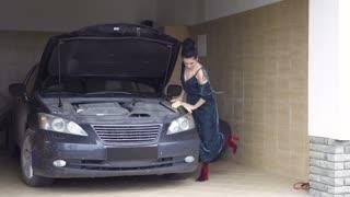 Beautiful woman wearing dress polishes car headlamp with rag