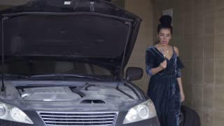Beautiful woman wearing dress tries to repair her luxury auto with wrenches