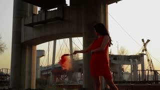 Beautiful woman wearing red dress dancing at sunset under abandoned bridge