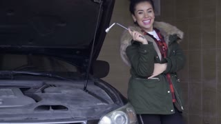 Beautiful woman with wrench in hand posing for camera leaning on car in garage
