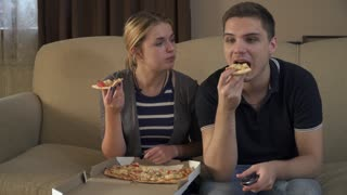 Beautiful young couple sitting on the couch and eating pizza
