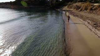 Beautiful young girl runs along the beach near the ocean