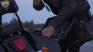 Biker take instruments from motorcycle trunk