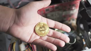 Bitcoin in male hand, computer cooler on blurred background