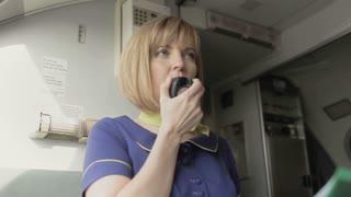Blonde stewardess speaks to the loadspeaker in the cabin of airplane