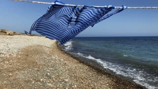 Blue dress dries on rope at sea background