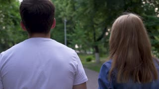 Boy and girl walk together at the park