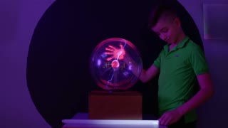 Boy conducts electricity and lights the lamp using his body and plasma globe