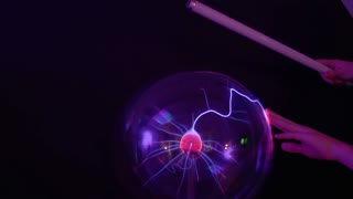 Boy touches to plasma globe with lamp
