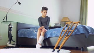Teenage boy making exercises, broken leg, plaster cast, recovery