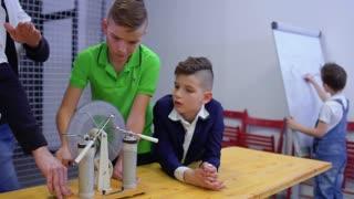 Boys and teacher explores wimshurst machine