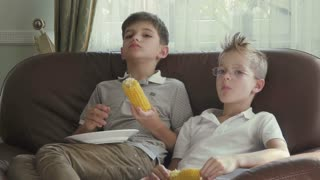 Boys are eating corn