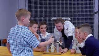 Boys examines wimshurst machine in laboratory